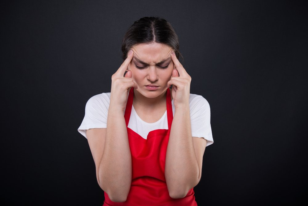 Distressed restaurant worker with red apron | Photo: Shutterstock