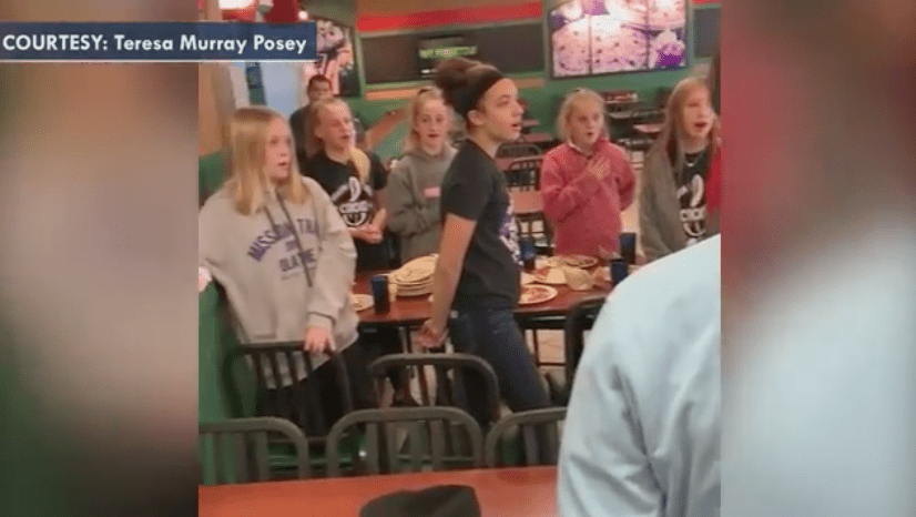 Middle school children singing to veteran Roy Fred Blackburn in a pizza joint. | Source: Fox News