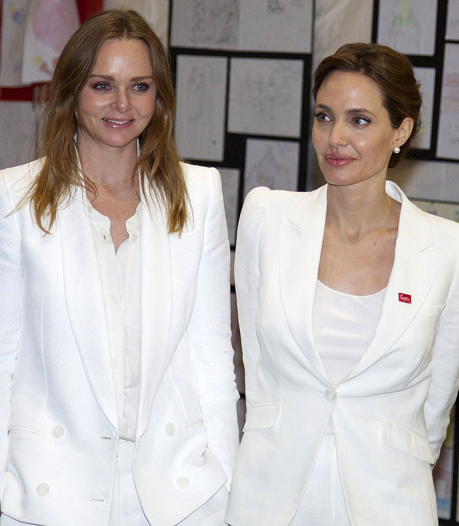 Stella McCartney and Angelina Jolie attend a photocall to launch War Child's 'Draw Me To Safety' campaign during the global conference to prevent sexual violence in conflict at ExCel on June 10, 2014 in London, England. | Source: Getty Images