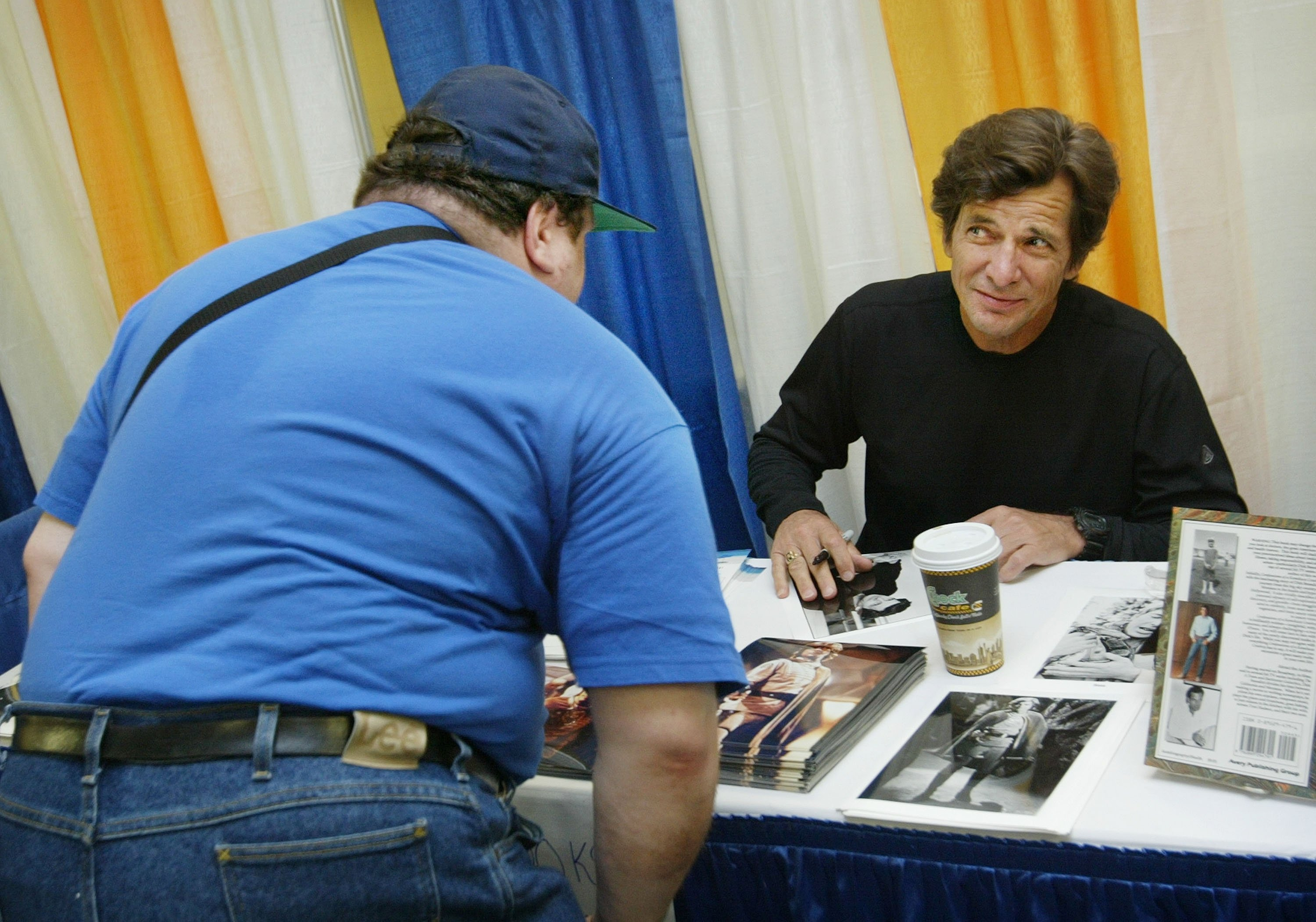 Actor Dirk Benedict, talks to a fan at the Sci-Fi and Fantasy Creators Convention June 27, 2003 | Source: Getty Images