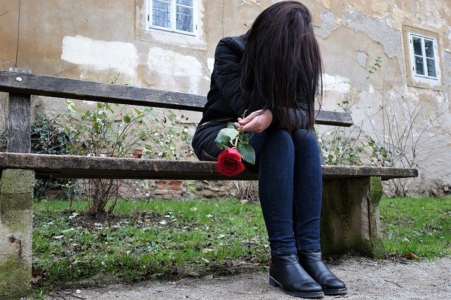 Sad woman holding a rose | Source: Pixabay