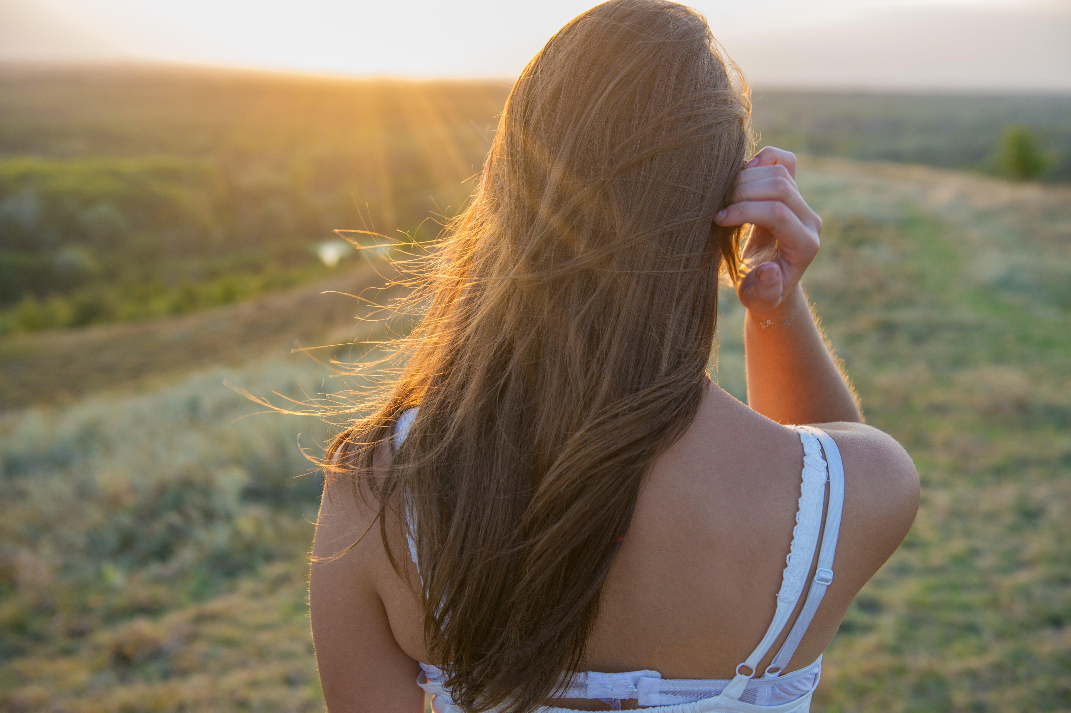 Une fille de dos au coucher du soleil dans la prairie. | Photo : shutterstock