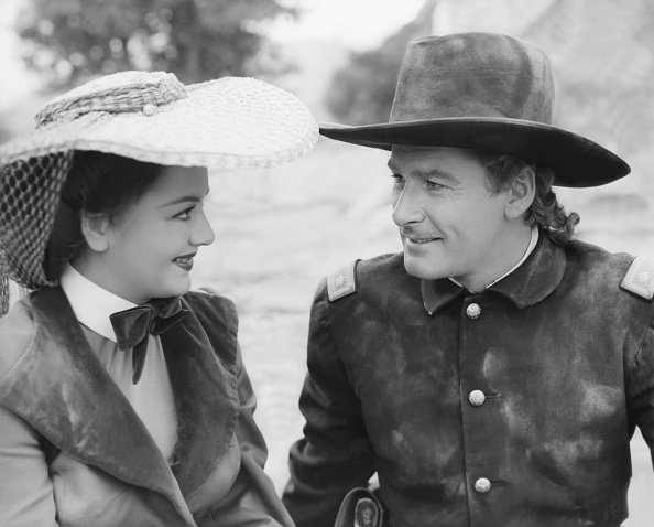 """Olivia de Havilland and Errol Flynn on the set of """"They Died with Their Boots On,"""" circa 1940s. 
