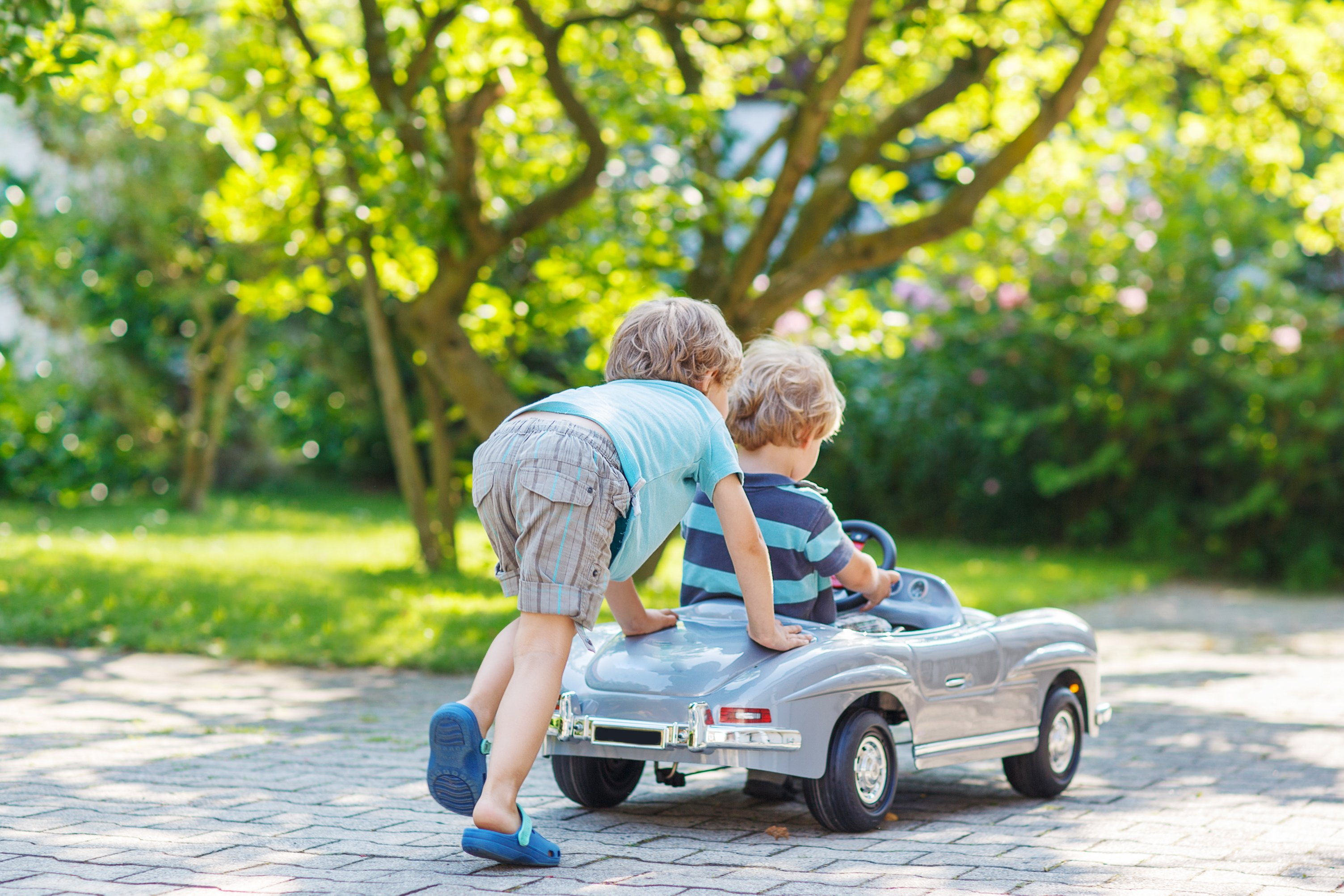 Two children playing with a toy car in a garden | Source: Shutterstock