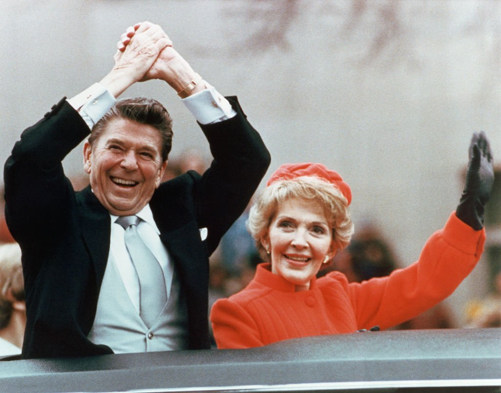 Ronald and Nancy Reagan waving and clasping hands in victory at Reagan's first inauguration, January 20, 1981.   Source: Getty Images