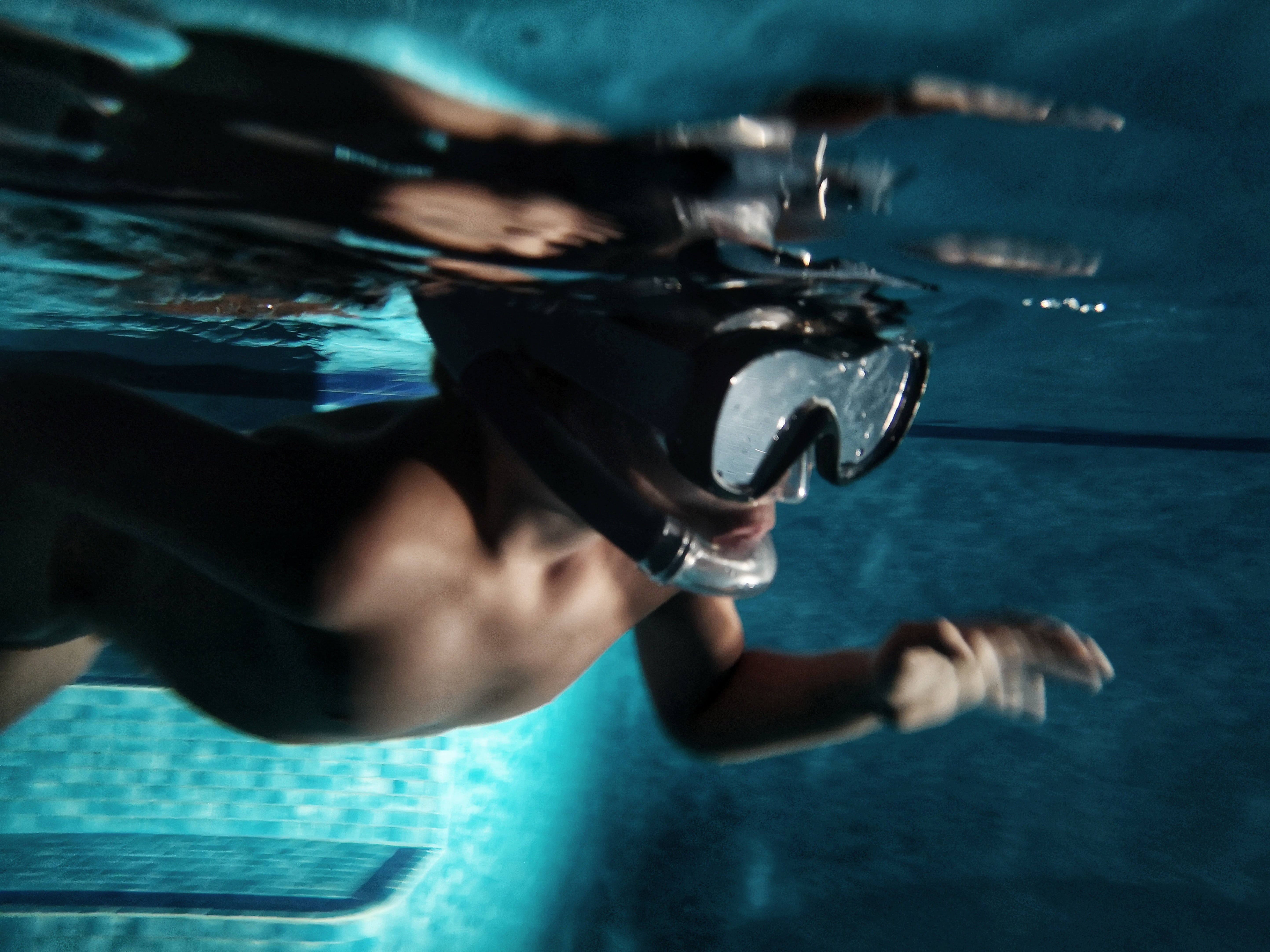 A diver with goggles on swims under the water   Photo: Unsplash/Alan Angelats