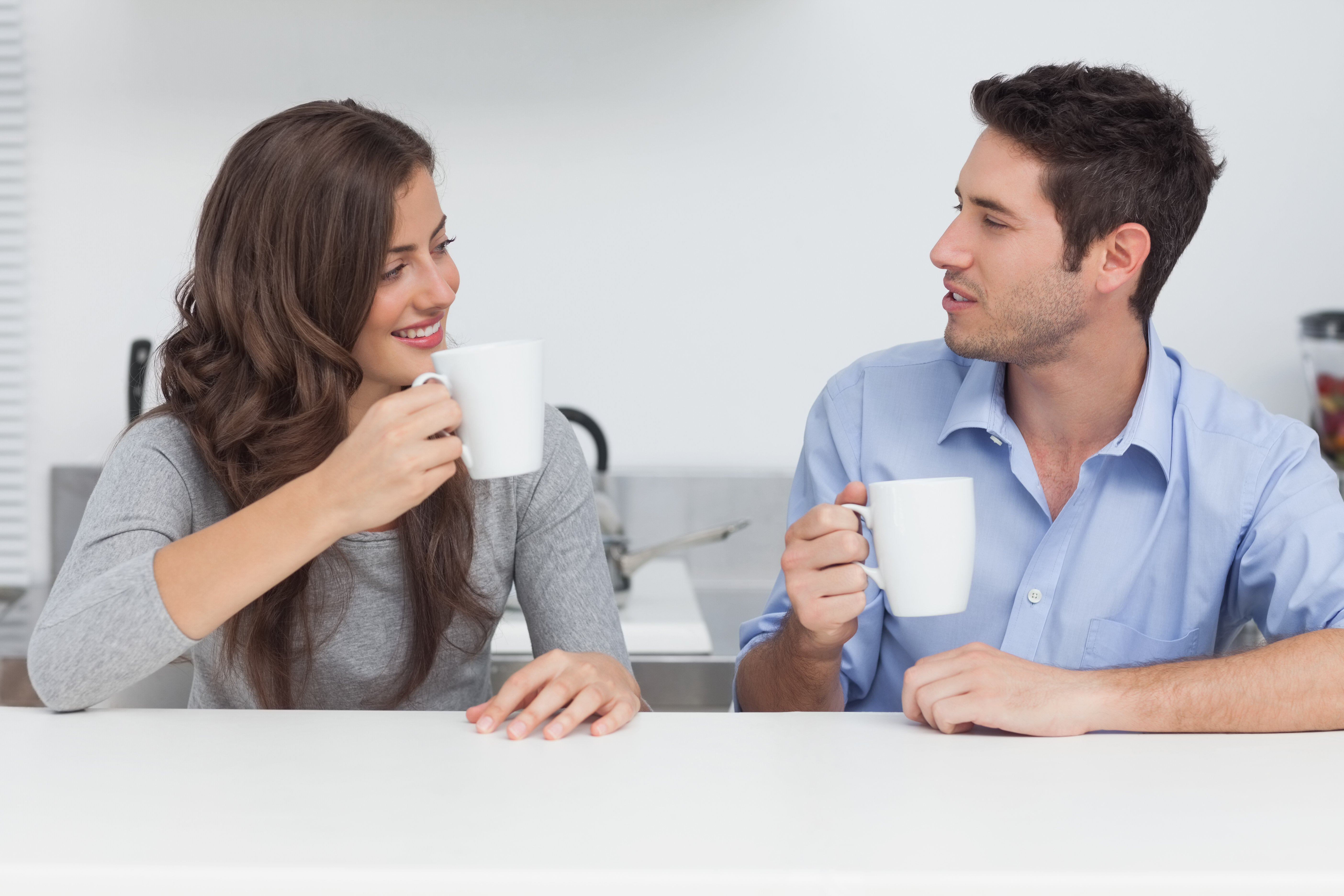 Couple drinking coffee in the kitchen | Photo: Shutterstock