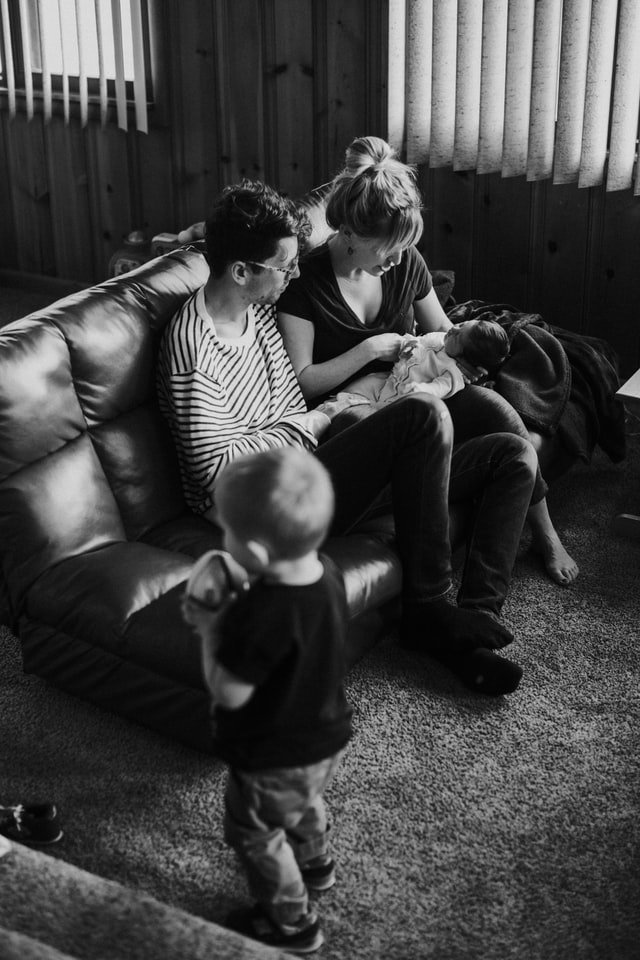 Black and white picture of family in living room | Source: Unsplash