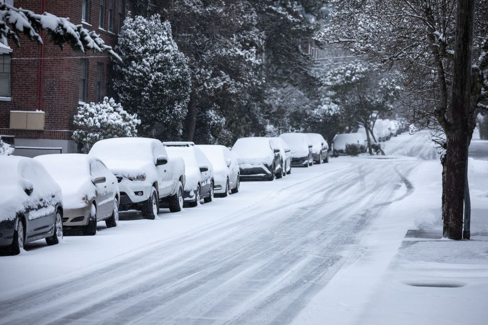 A snow covered street filled with snow covered cars. | Source: Shutterstock