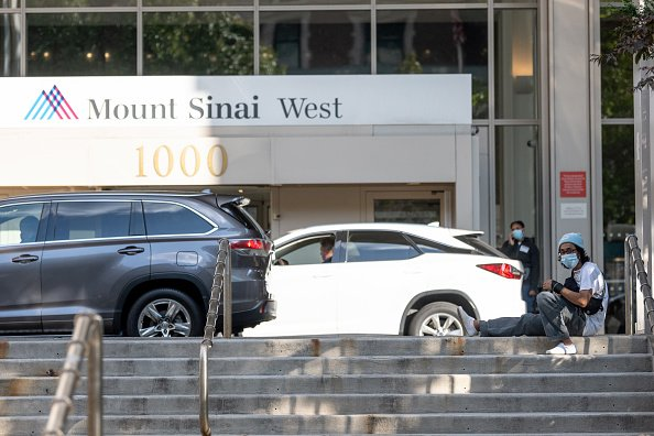 A man wearing a mask sits on the steps outside Mount Sinai West Hospital. | Photo: Getty Images