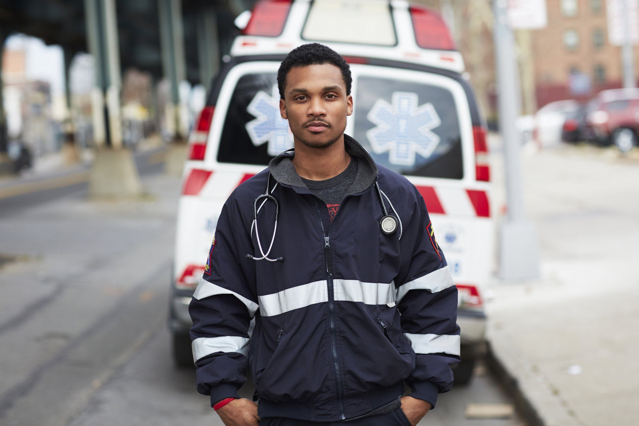 A picture of a male paramedic standing in front of an ambulance. | Photo: Getty Images