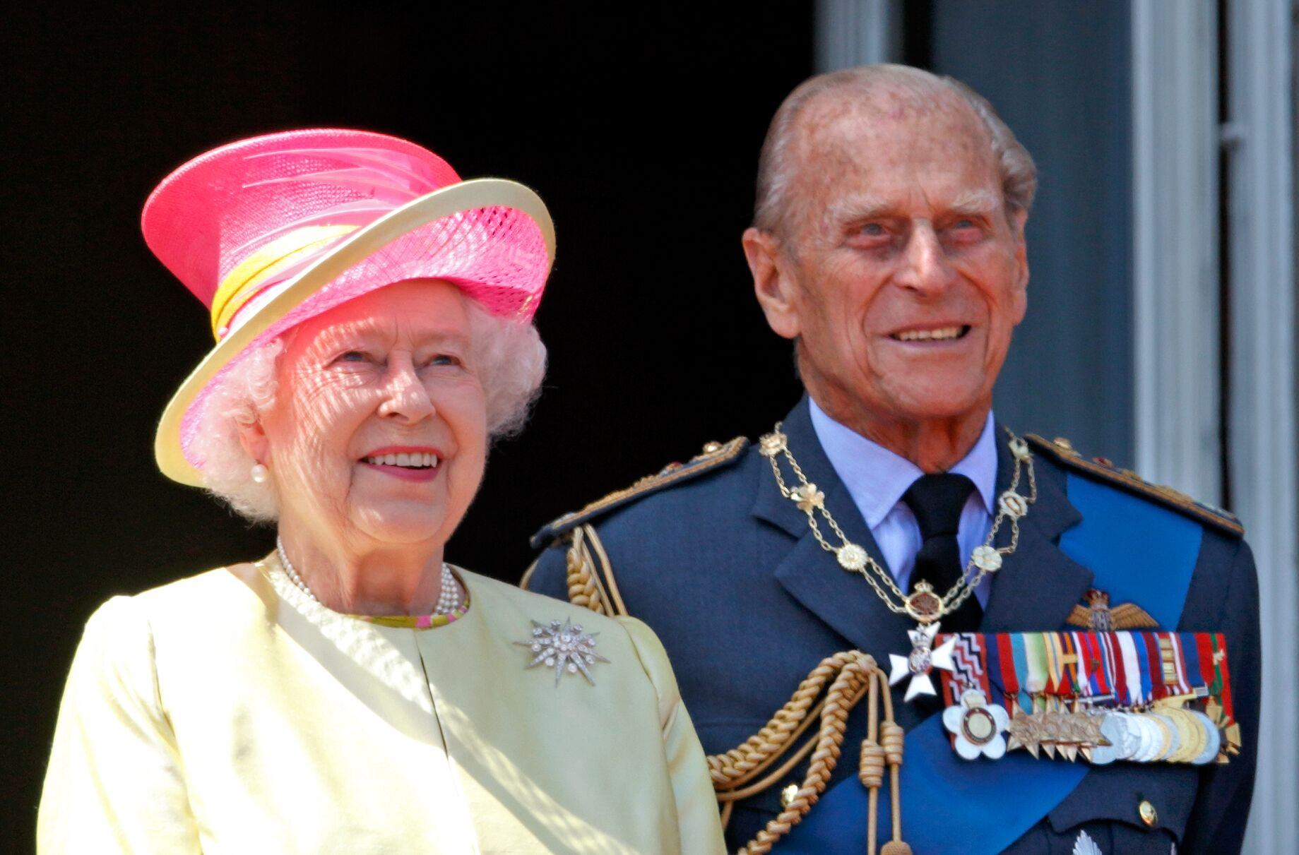 Queen Elizabeth II and Prince Philip, Duke of Edinburgh watch a flypast of Spitfire & Hurricane aircraft from the balcony of Buckingham Palace. | Source: Getty Images
