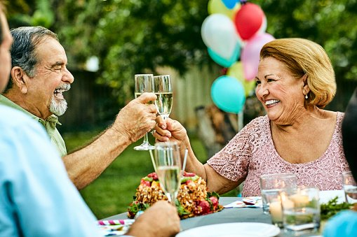 Photo of happy senior couple toasting champagne flutes while sitting at dining table. | Photo: Getty Images