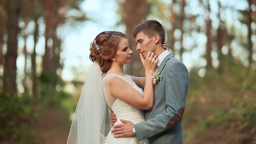 Photo of a young couple in their wedding dress with forest as the background | Photo: Shutterstock