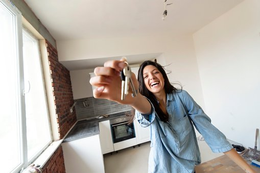 Photo of a happy woman holding keys to her new house | Photo: Getty Images