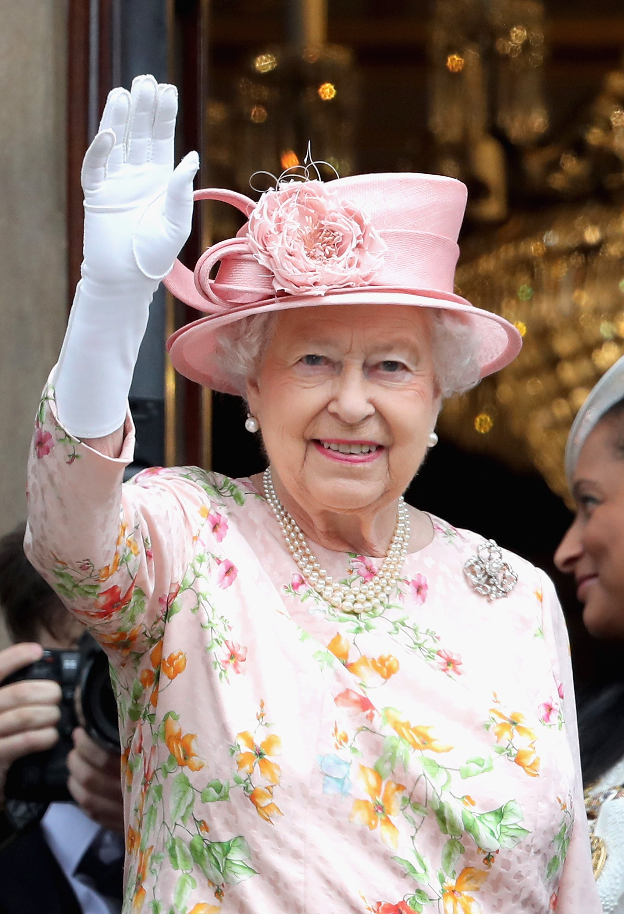 Queen Elizabeth II waves from the balcony of the Town Hall during a visit to Liverpool on June 22, 2016, in Liverpool, England. | Source: Getty Images.