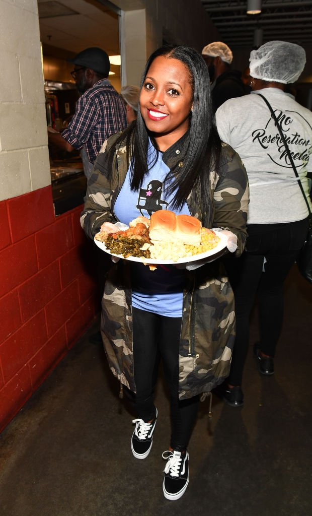 """Keisha Knight Pulliam shows off a plate of food at the """"No Reservations Needed Thanksgiving Dinner"""" at The Shepherd's Inn, on November 20, 2018, in Atlanta, Georgia 
