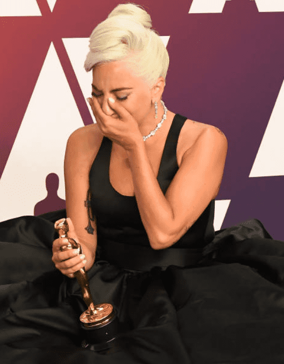 Lady Gaga sits on the floor in her gown and cries after receiving an oscar at the 91st Annual Academy Awards, on February 24, 2019,  in Hollywood, California | Source: Getty Images (Photo by Steve Granitz/WireImage )
