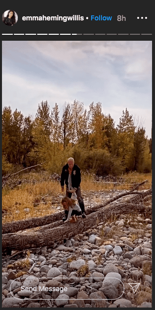 Photo of Bruce Willis holding Evelyn's hand while she bent to pick something from the log of wood | Photo: Instagram / emmahemingwillis