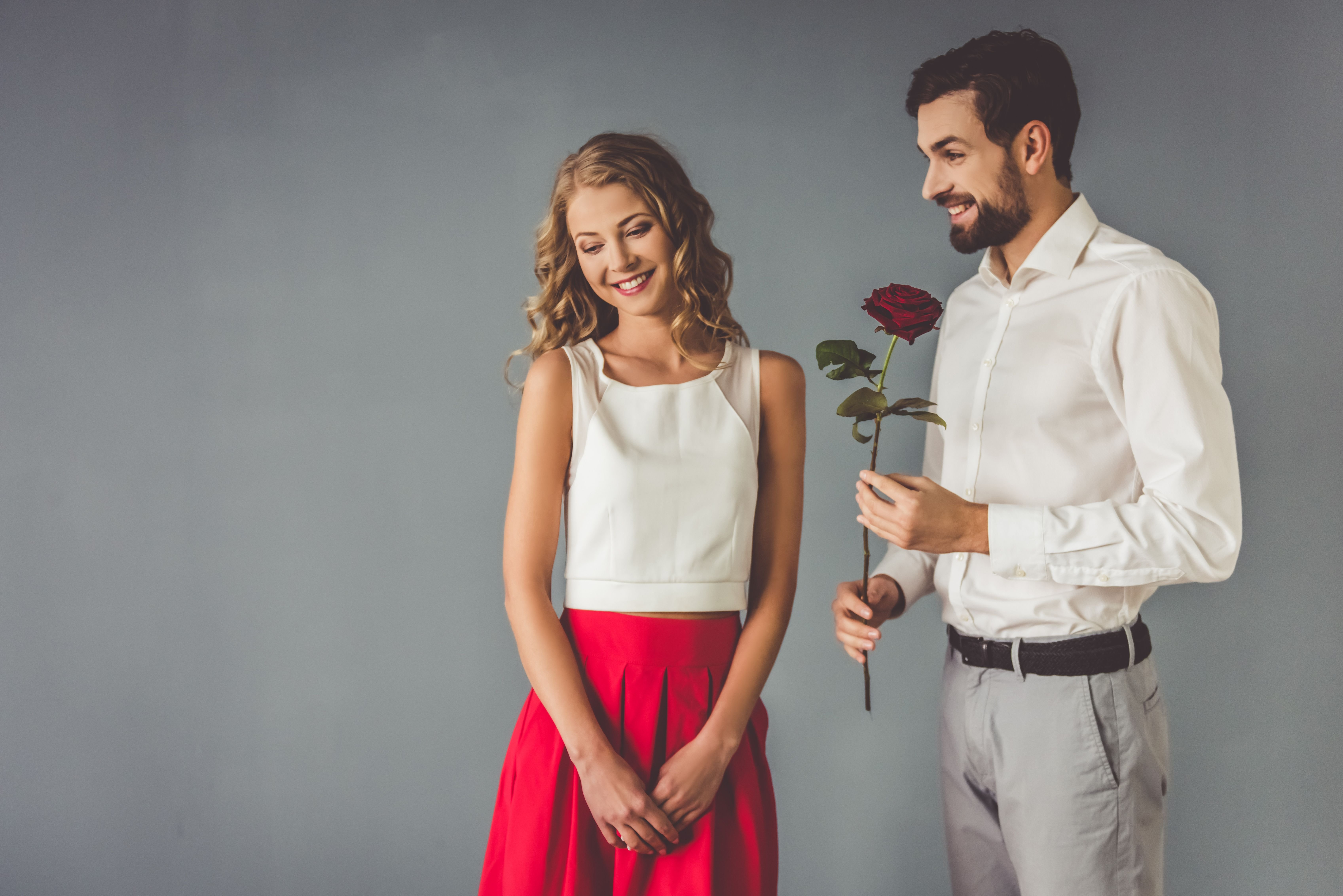 A man gives a woman red flowers.  Source: Shutterstock
