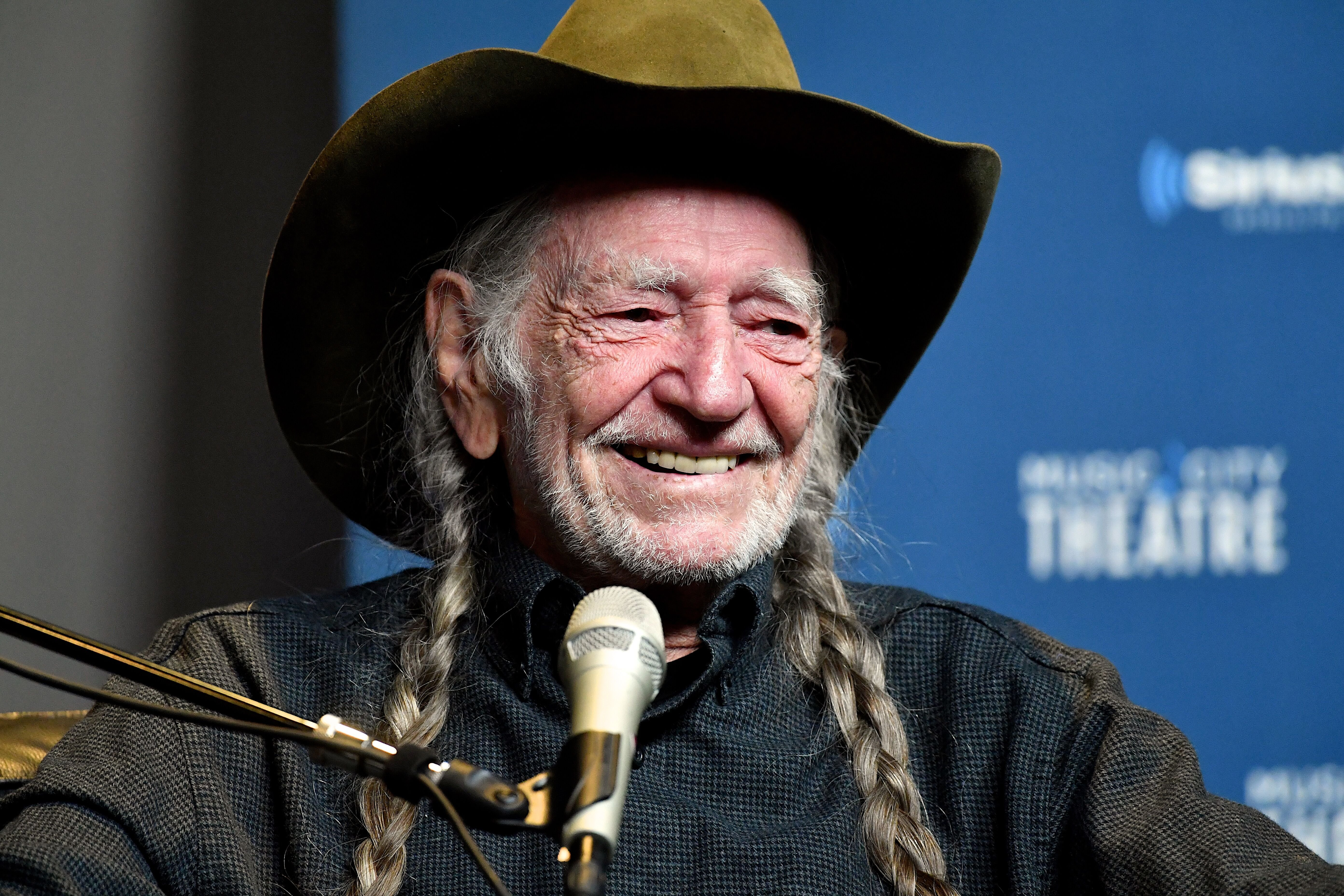 Willie Nelson speaks onstage at his album premiere. | Source: Getty Images