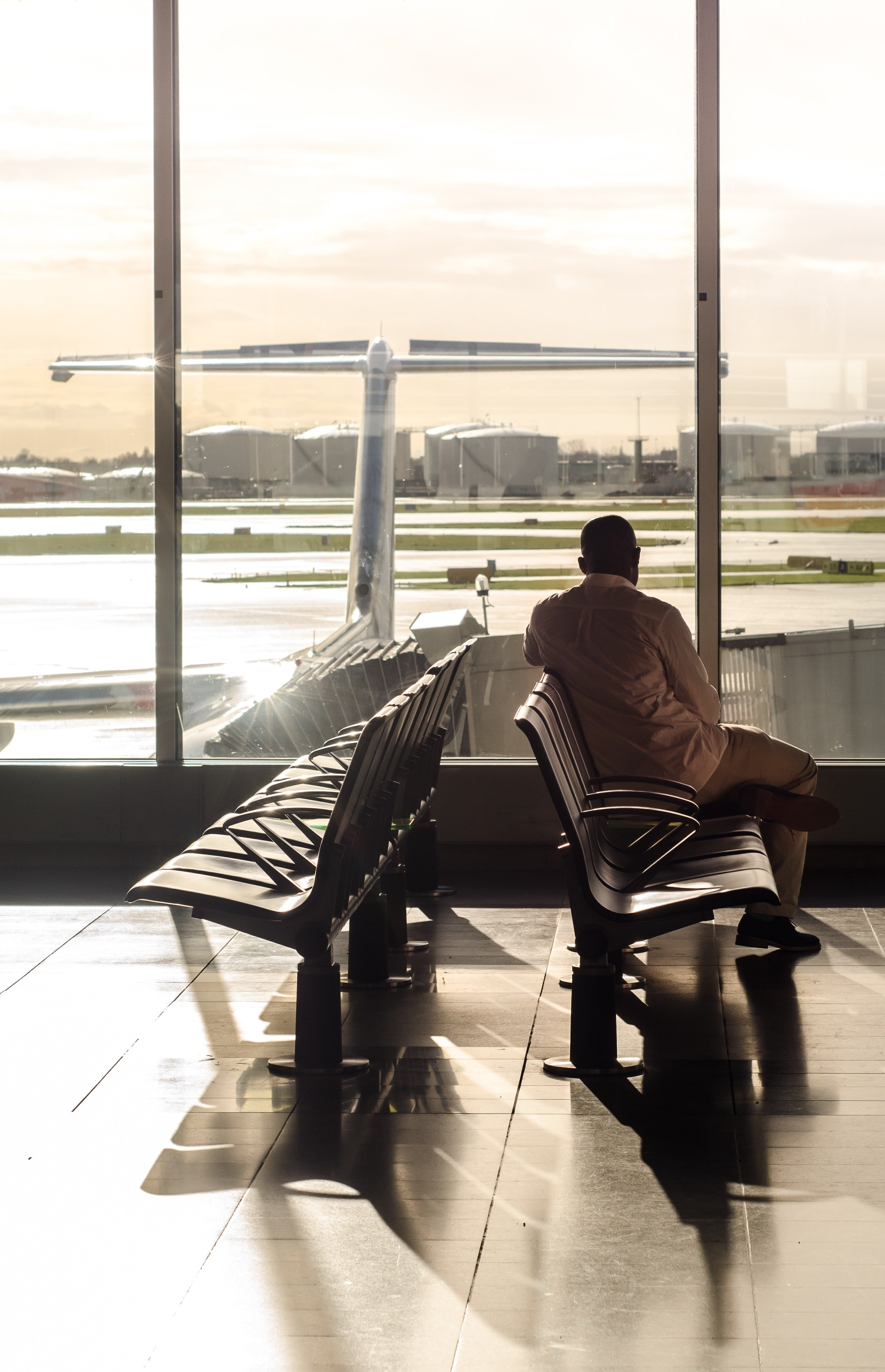 A photo of a man at the airport waiting for his flight. | Photo: Pexels