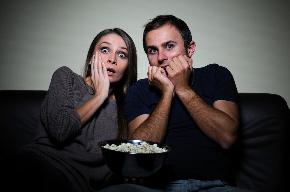 Young couple watches scary movie with popcorn | Photo: Shutterstock