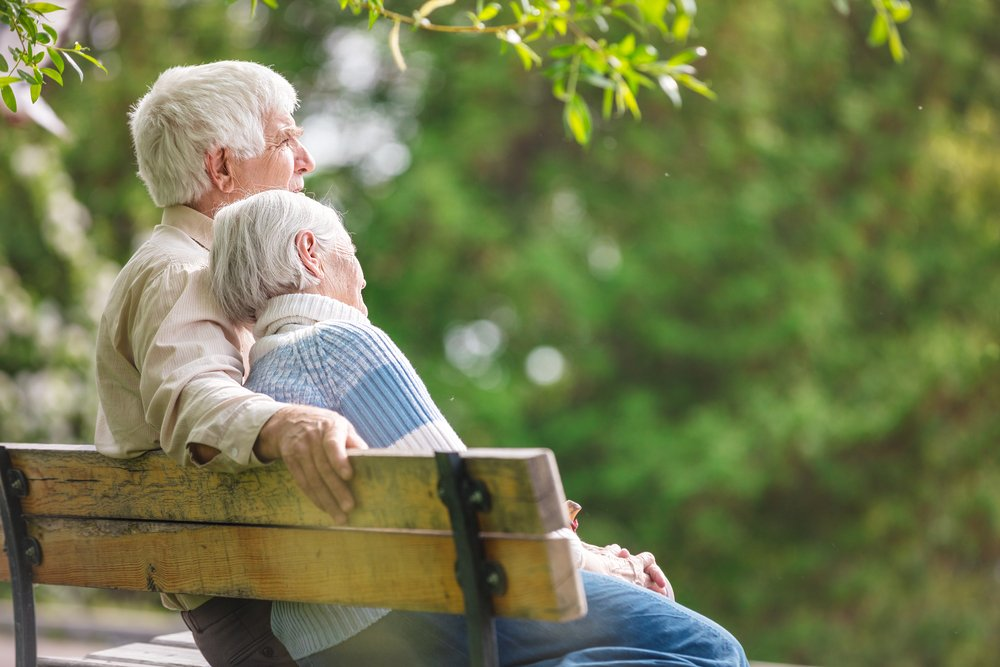 An elderly couple resting on a bench in the park looking at nature. | Photo: Shutterstock.