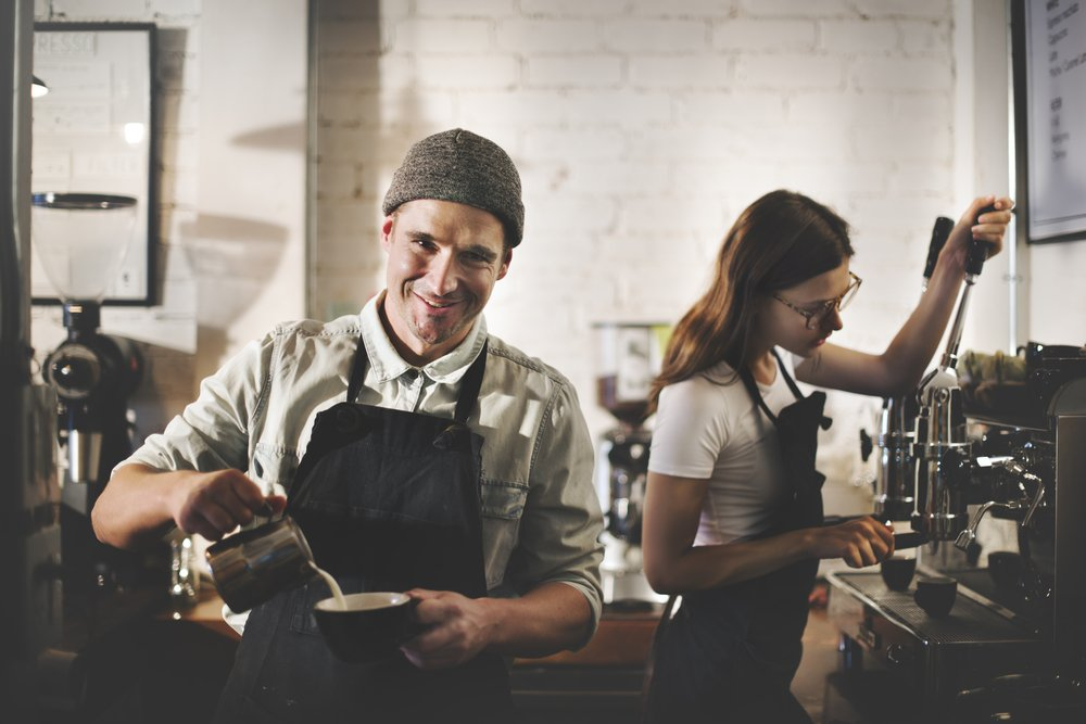 A barista in an apron while using a machine in a coffee shop. | Photo: Shutterstock.