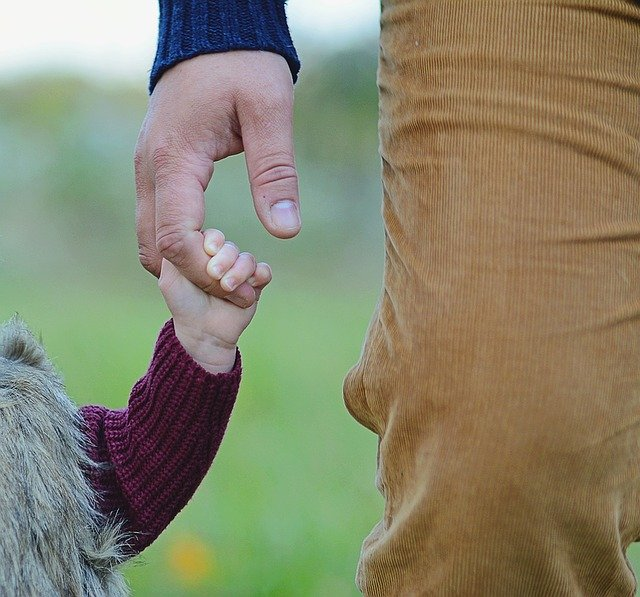 Man holds his daughter's hand while walking | Photo: Pixabay