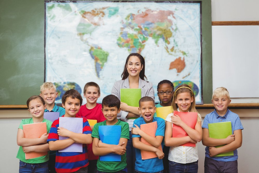Students standing with the teacher at the elementary school | Photo: Shutterstock