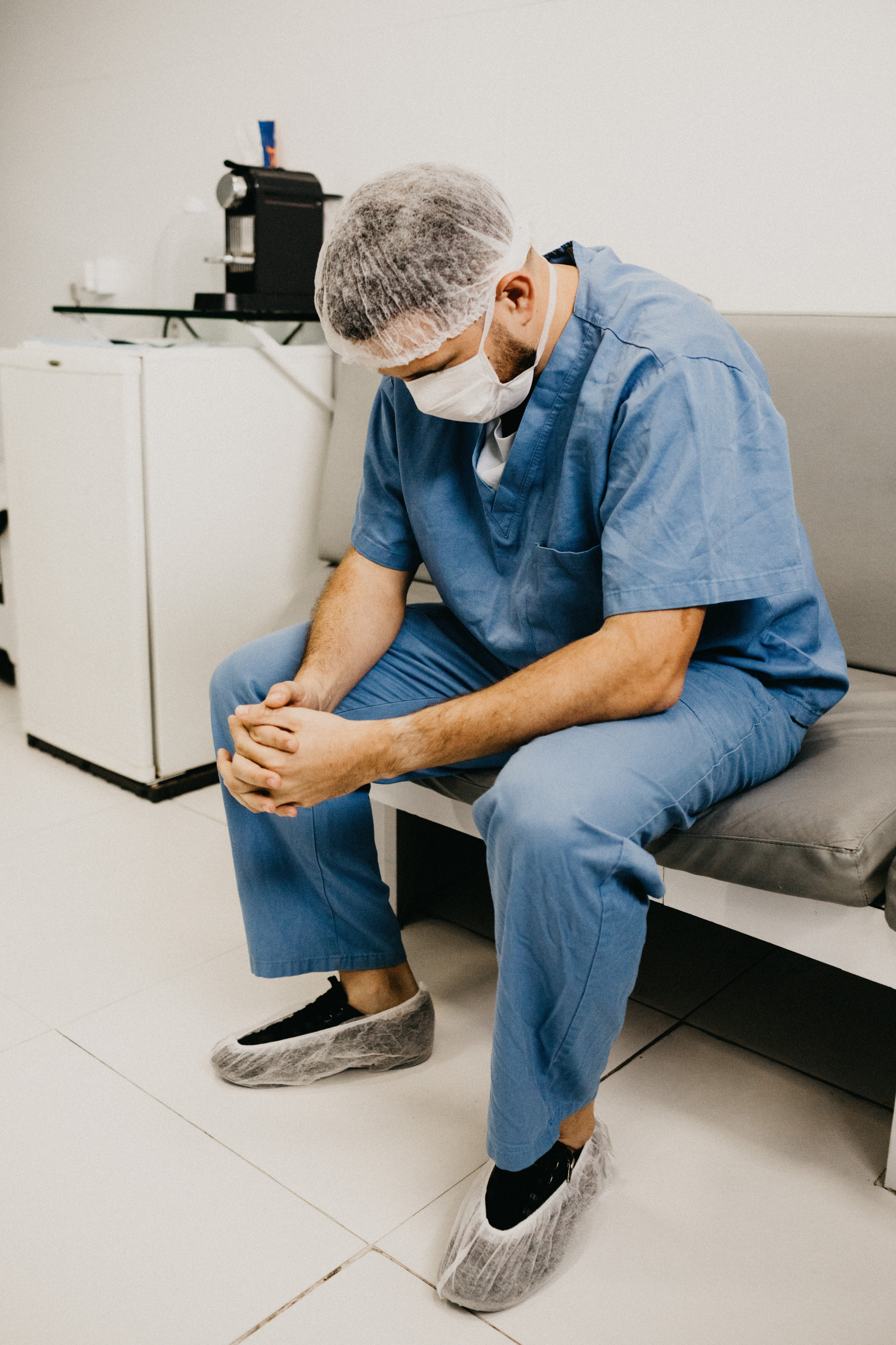 A medical professional sitting on a bench in their scrubs. | Source: Pexels