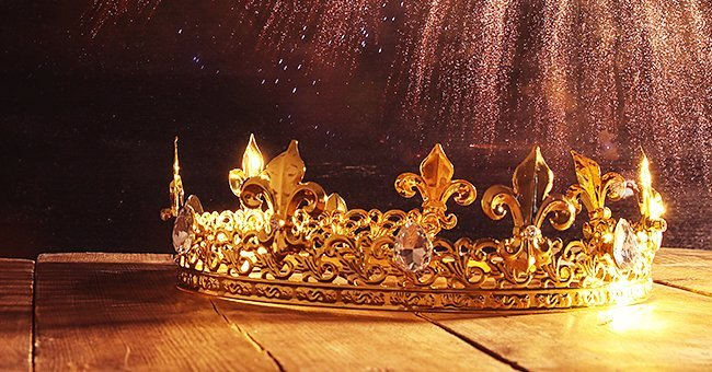 Photo of a golden crown placed on a wooden surface | Source: Shutterstock