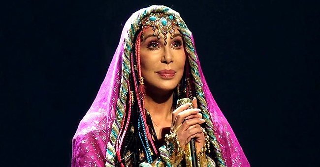 Cher Looks Unforgettable Posing in a Pink Opera Cloak & Headband Adorned with Gemstones