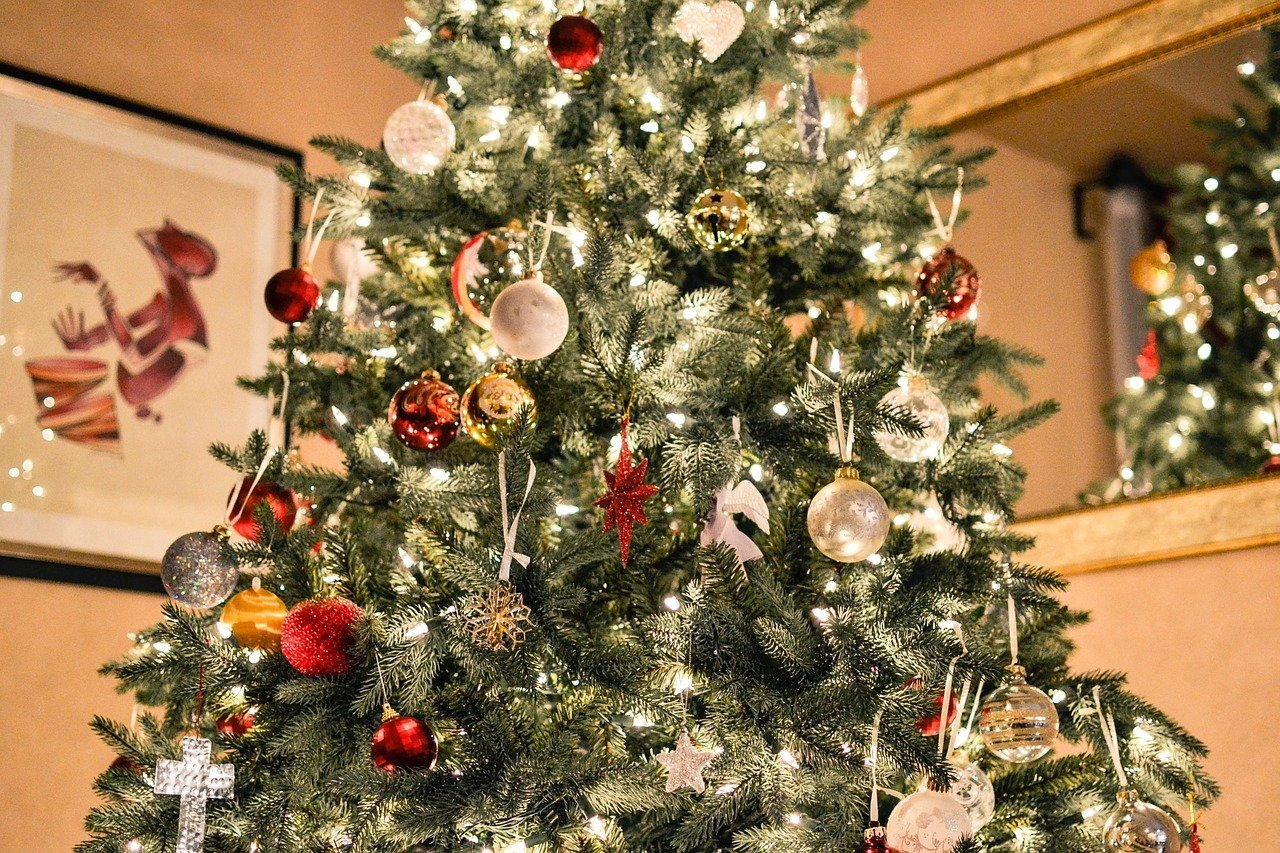 A fully decorated Christmas tree, complete with lights, in a living room. Photo: Pixabay