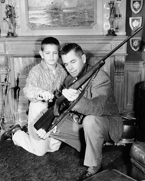 Glenn Ford montrant un fusil a son fils Peter Ford.   Getty images