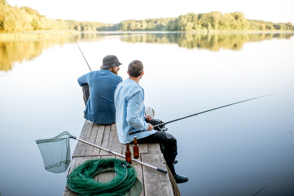 A photo of two male friends fishing together. | Photo: Shutterstock.