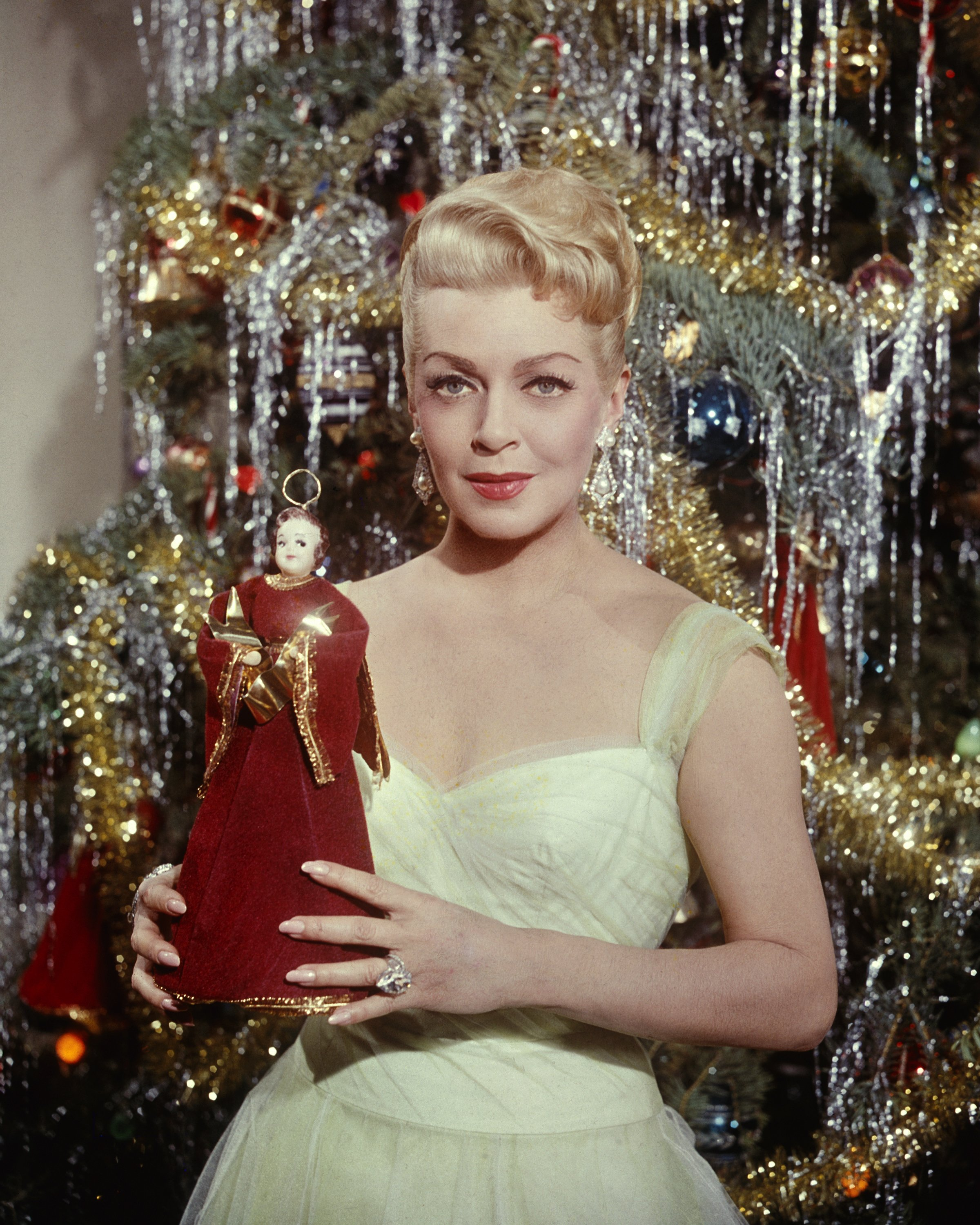 American actress Lana Turner (1921 - 1995) holding the angel from the top of a Christmas tree, circa 1965.| Source: Getty Images