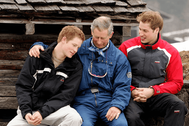 Prince Charles hugs his son Prince Harry while joined by Prince William during a holiday at Klosters on March 31, 2005, Switzerland | Source: Pascal Le Segretain/Getty Images