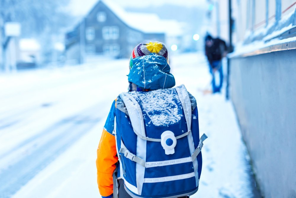 Boy walks along snowy streets | Photo: Shutterstock