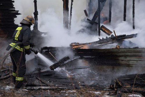 Fireman spraying water in a smouldering burnt out house.| Photo: Shutterstock.