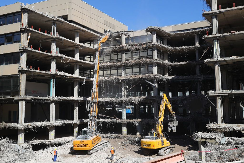 A Longfront excavator with demolition shears demolishes a multilevel office building in Germany. | Source: Getty Images