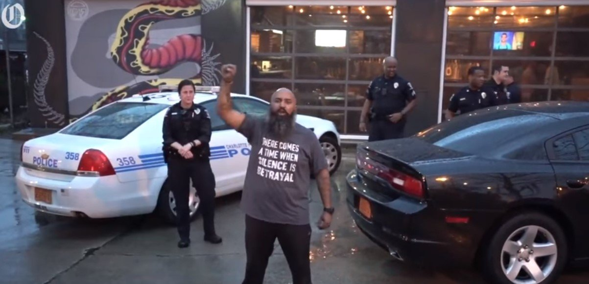 "Andrew Woods leading a protest at the ""Pizza Peel"" in Midwood Plaza, N.C. 