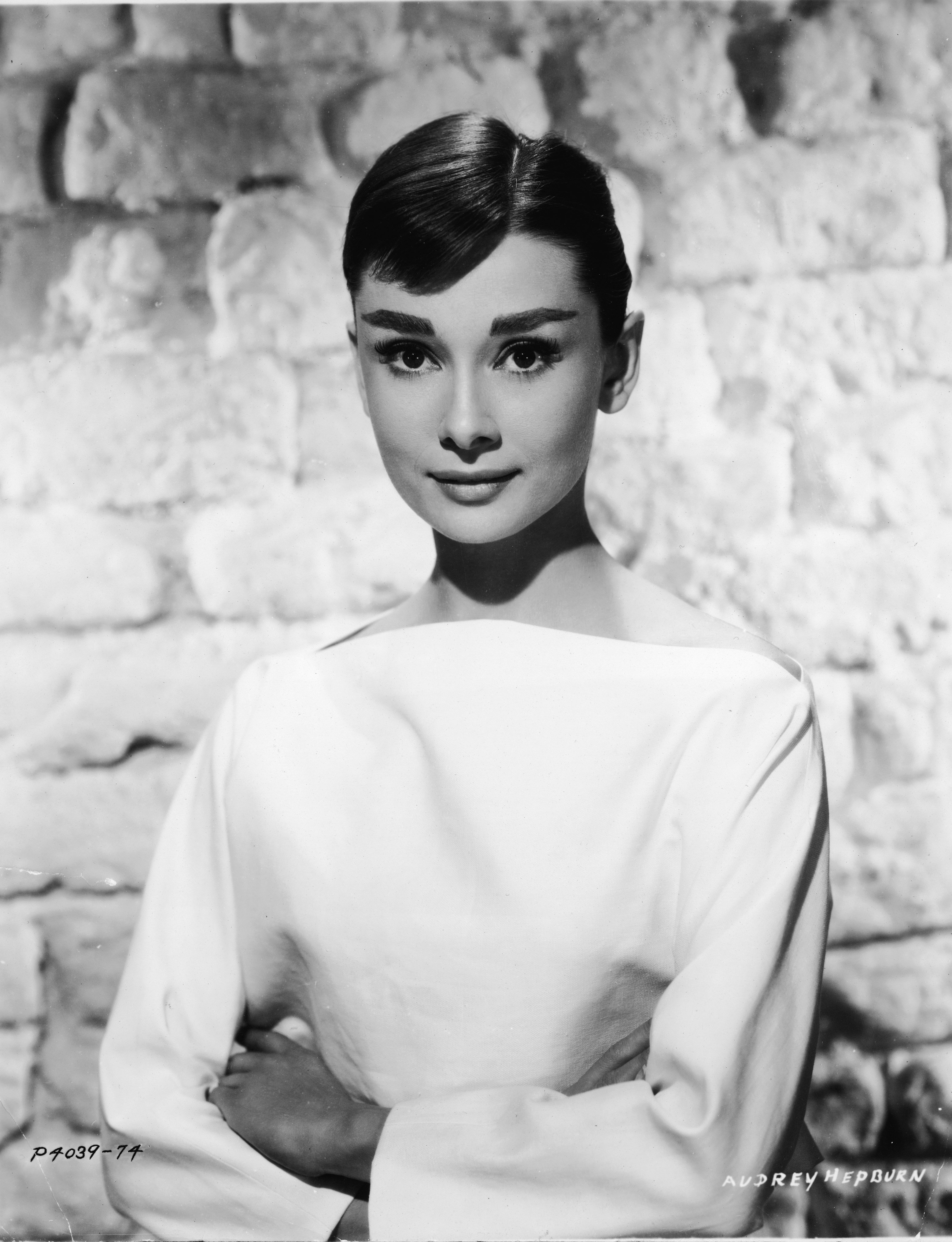 American actress Audrey Hepburn circa 1955 in a white long-sleeved dress. | Getty Images
