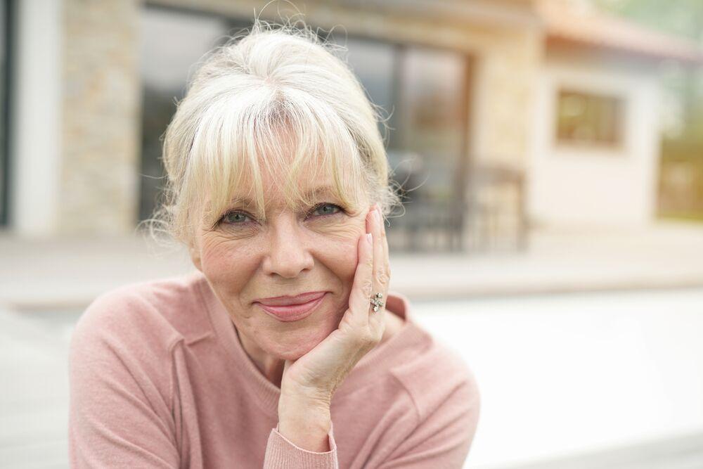 Femme âgée regardant dans l'appareil photo et souriant   Photo : Shutterstock
