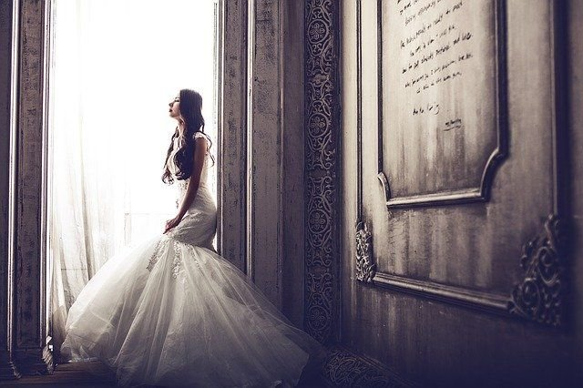 A woman wearing a bridal dress while looking out the window. | Source: Shutterstock