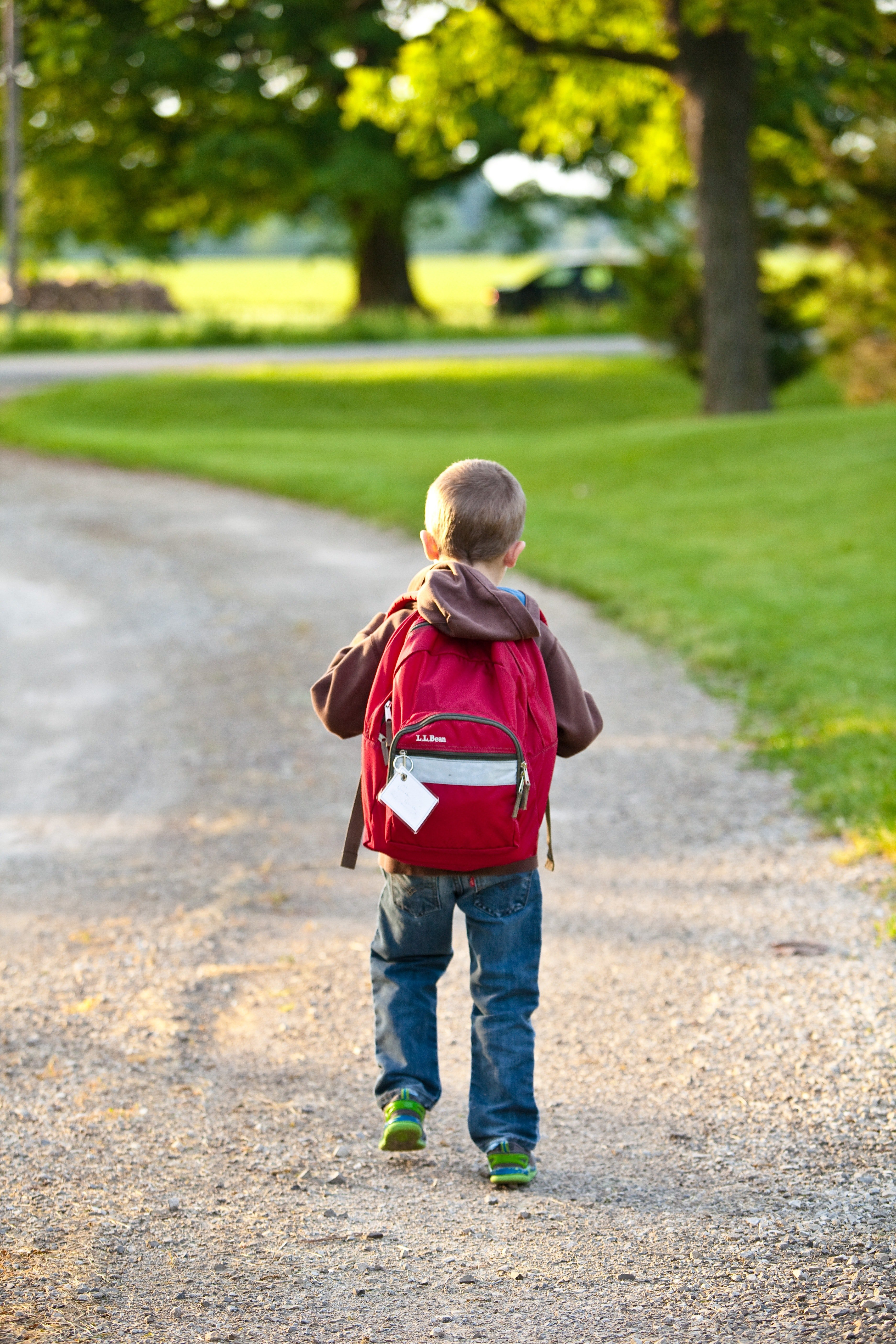 A young boy walking to school carrying his backpack. | Source: Pexels