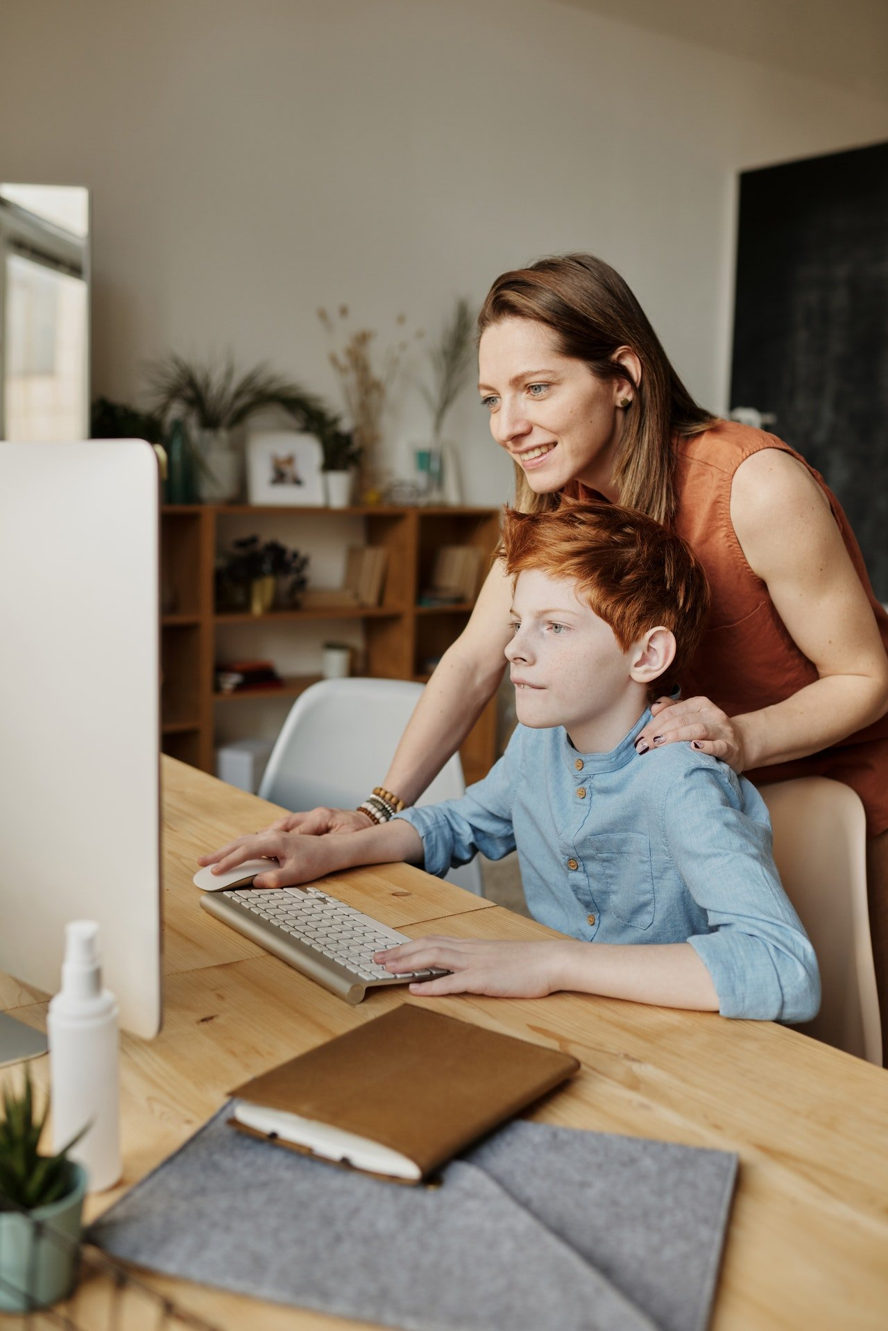 Mother helping her son out with the computer | Photo: Pexels