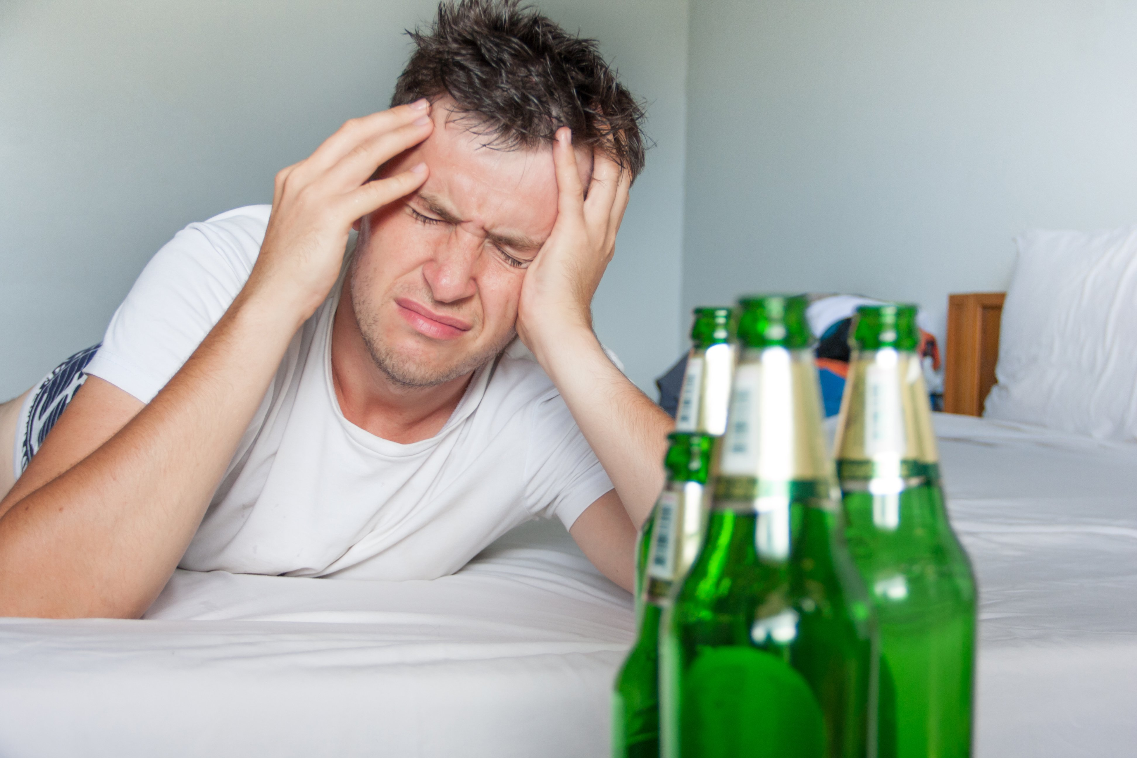 Man suffering from a hangover whileholding his aching head | Photo: Shutterstock/Michael Traitov