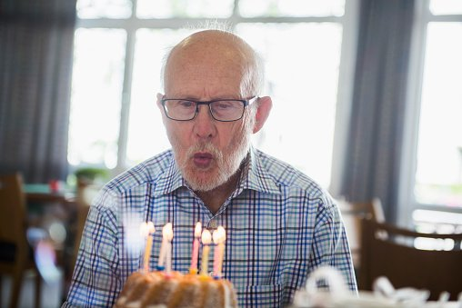 Photo of an elderly man  blowing out birthday candles | Photo: Getty Images